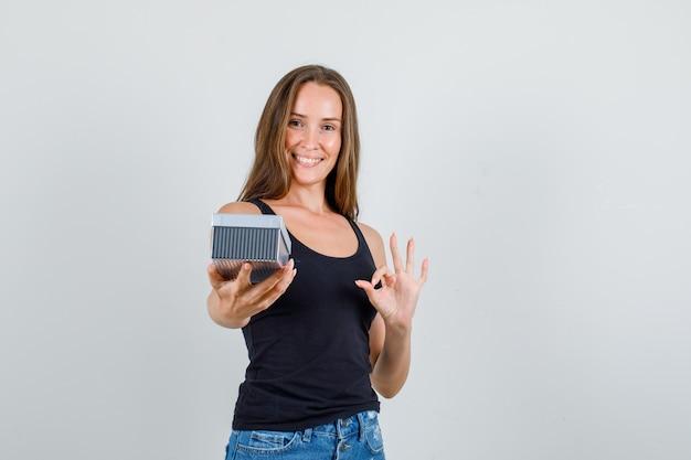 Mulher jovem em camiseta e shorts segurando uma caixa de presente com um sinal de ok e parecendo alegre