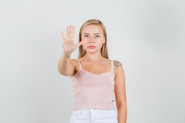 Mulher jovem em camiseta, minissaia, mostrando o sinal de pare com a mão e parecendo séria