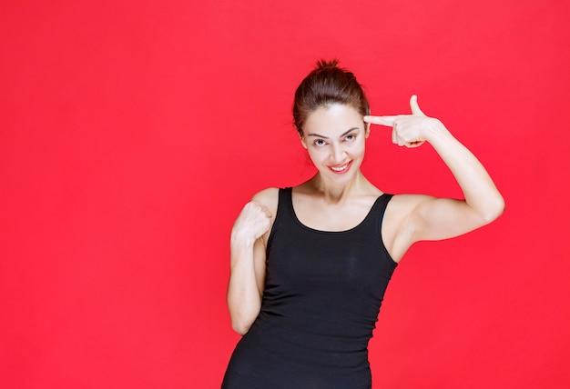 Mulher jovem em camiseta preta em pé na parede vermelha e pensando