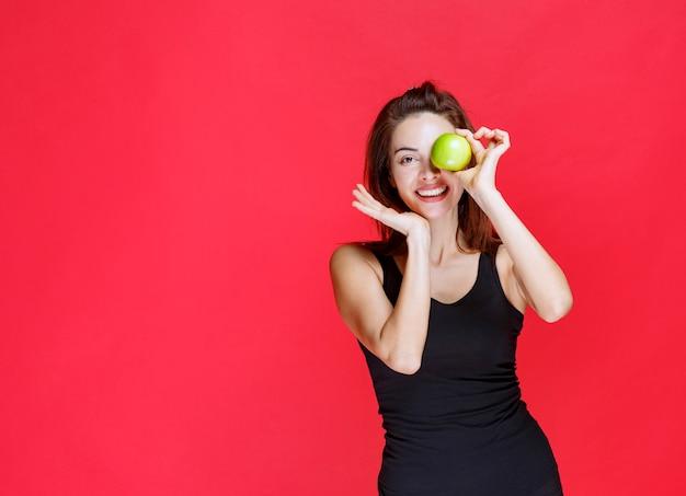 Mulher jovem em camiseta preta segurando maçãs verdes no olho