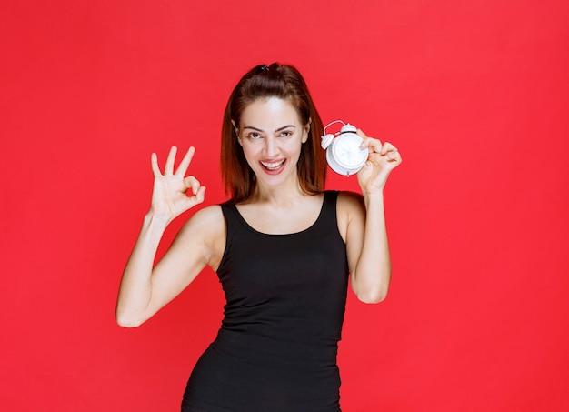 Mulher jovem em camiseta preta segurando um despertador e mostrando um sinal positivo com a mão