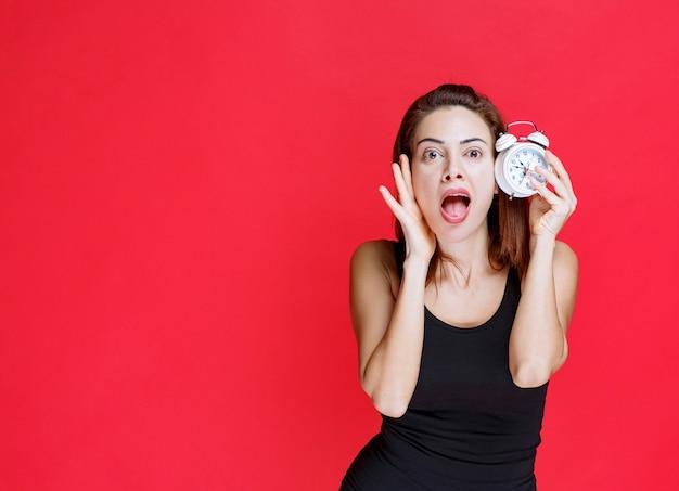 Mulher jovem em camiseta preta segurando um despertador e parece apavorada e surpresa