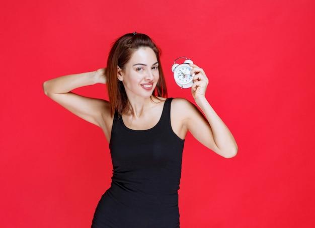 Mulher jovem em camiseta preta segurando um despertador e parece pensativa