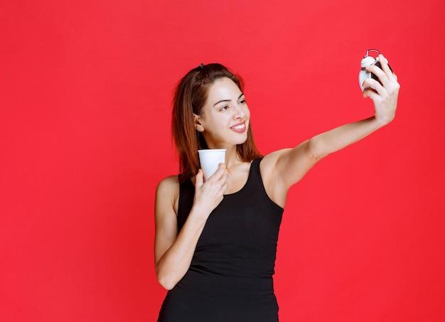 Mulher jovem em camiseta preta segurando um despertador e um copo de bebida