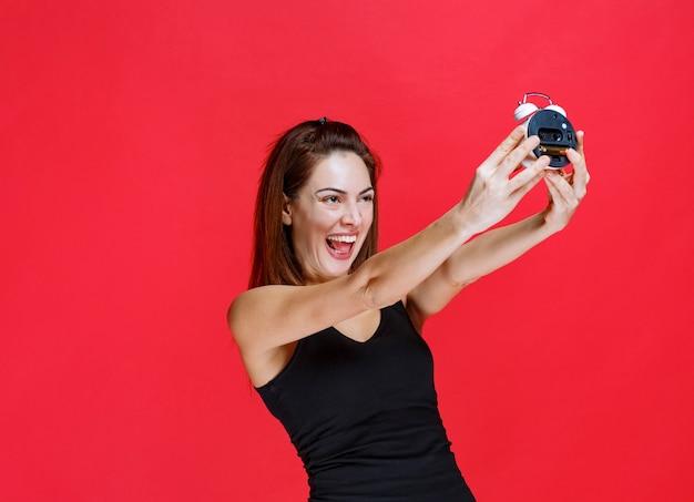 Mulher jovem em camiseta preta segurando um despertador, verificando e se sentindo bem