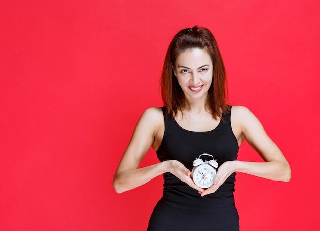 Mulher jovem em camiseta preta segurando um despertador