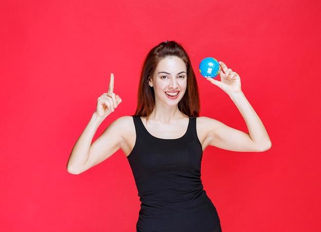 Mulher jovem em camiseta preta segurando um mini-globo mundial e encontrando lugares nele