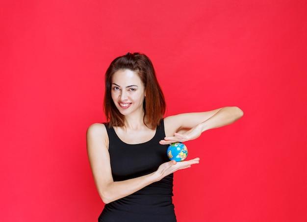 Mulher jovem em camiseta preta segurando um mini-globo mundial
