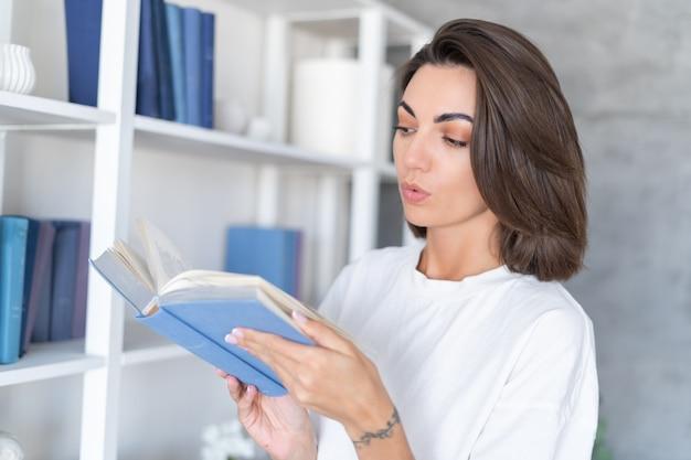 Mulher jovem em casa com uma camiseta branca perto de uma estante de livros segurando um livro e escolhe o que ler em uma noite de inverno e outono