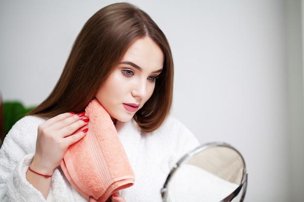 Mulher jovem em casa na frente de um espelho enxuga o rosto após tratamentos de spa.