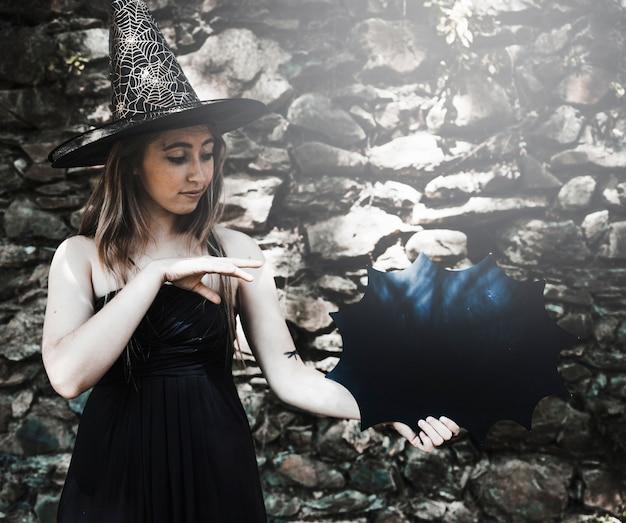 Mulher jovem, em, chapéu bruxa, mostrando, magia, com, dia das bruxas, decoração