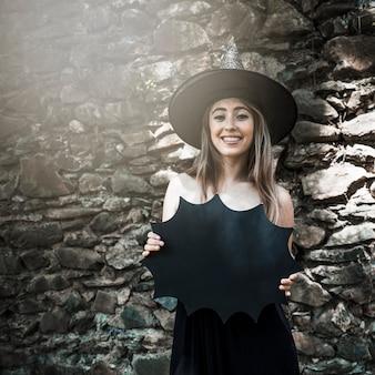 Mulher jovem, em, chapéu bruxa, segurando, decoração halloween