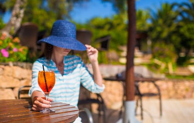 Mulher jovem, em, chapéu, sentando, em, tropicais, café, perto, piscina