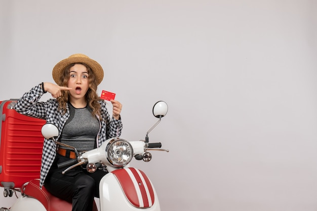 Mulher jovem em ciclomotor apontando para o cartão de frente