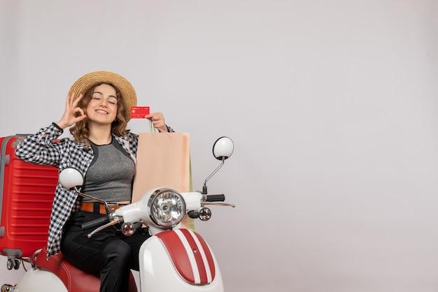 Mulher jovem em ciclomotor segurando cartão fazendo sinal de ok