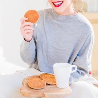 Mulher jovem, em, cinzento, suéter, comer, biscoitos