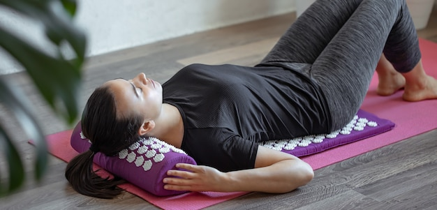 Mulher jovem em colchonete em casa de massagem de acupuntura