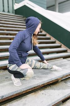 Mulher jovem, em, com capuz, topo, esticar, dela, perna, ligado, escadaria