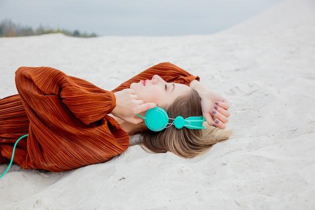 Mulher jovem, em, cor borgonha, blusa, com, fones, deitando-se