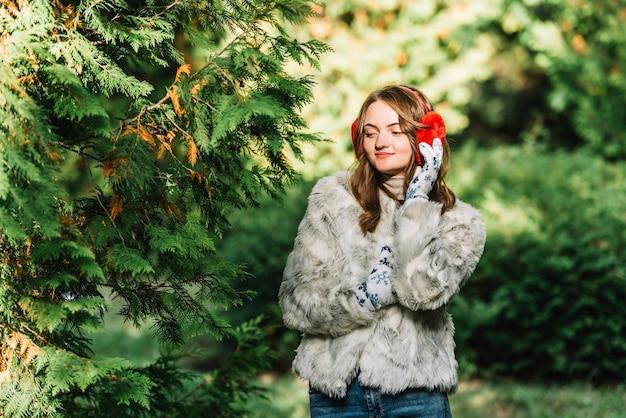 Mulher jovem, em, earmuffs, perto, coniferous, ramos