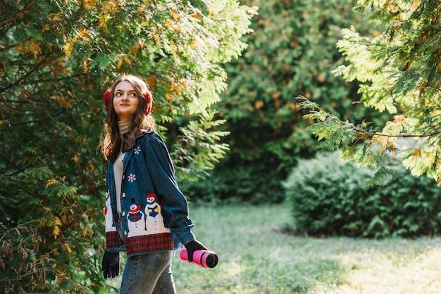 Mulher jovem, em, earmuffs, segurando, garrafa térmica, perto, galhos verdes