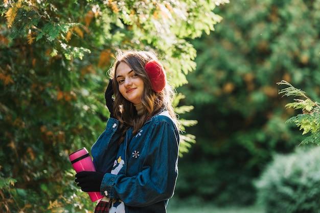 Mulher jovem, em, earmuffs, segurando, thermos, perto, ramos