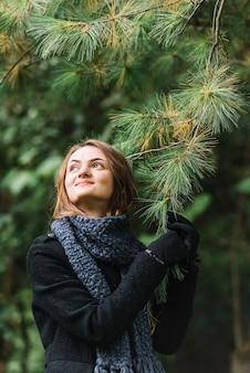 Mulher jovem, em, echarpe, segurando, coniferous, ramo