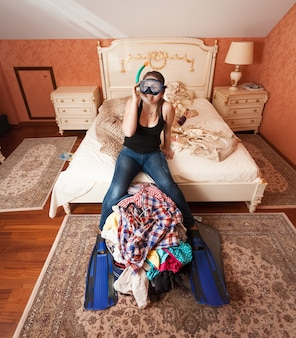 Mulher jovem em equipamento de mergulho com snorkel sentada em uma sacola desempacotada