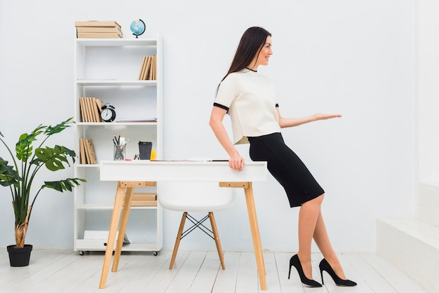 Mulher jovem, em, escritório, segurando, algo, ligado, palma