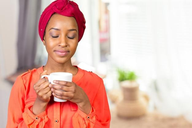 Mulher jovem, em, escritório, segurando copo