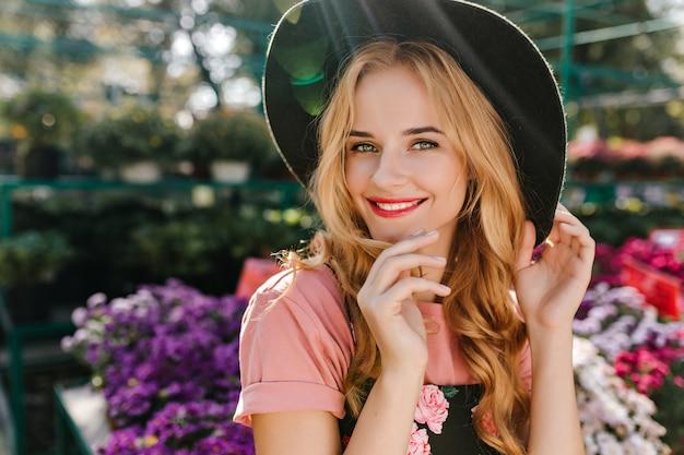Mulher jovem em êxtase com olhos claros, se passando perto de flores. linda mulher europeia com chapéu relaxando na laranjeira.