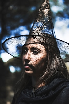 Mulher jovem, em, feiticeiro, chapéu, e, capa, olhando, em, floresta