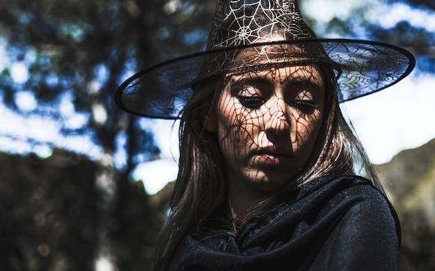 Mulher jovem, em, feiticeiro, chapéu, e, manto, olhar baixo, em, floresta