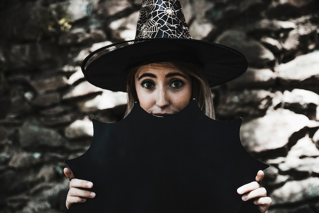 Mulher jovem, em, feiticeiro, chapéu, segurando, decoração halloween