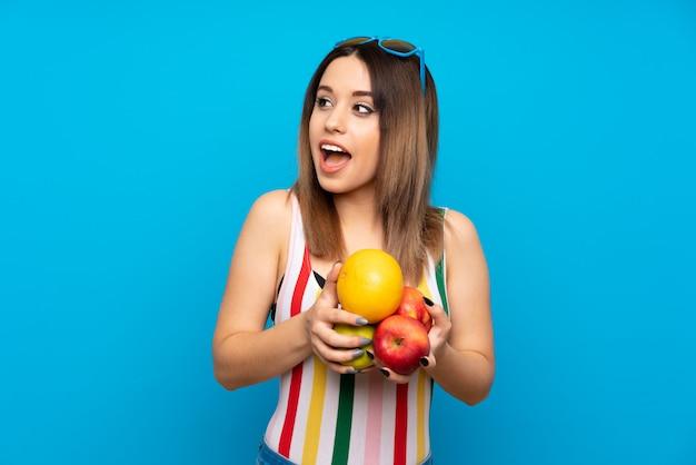 Mulher jovem, em, férias verão, sobre, azul, segurando, frutas