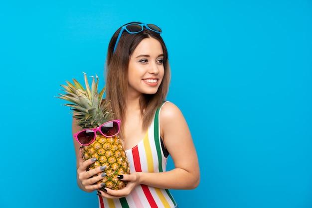Mulher jovem, em, férias verão, sobre, azul, segurando, um, abacaxi, com, óculos de sol