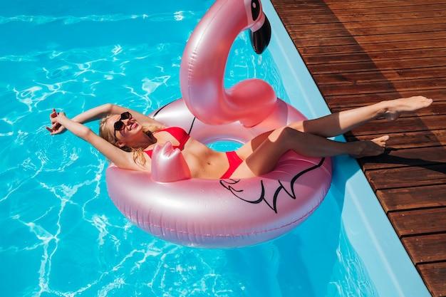 Mulher jovem, em, flamingo, anel nadada, posar