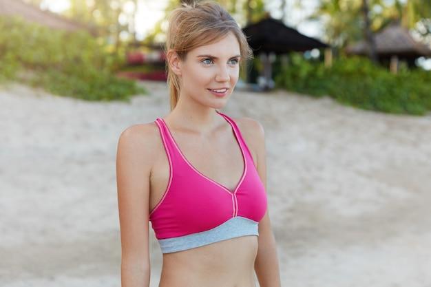 Mulher jovem em forma com fato de treino rosa descansa depois de uma corrida matinal intensa na praia, tem corpo perfeito, faz uma pausa. corredor feminino atlético atraente tem corrida ativa, envolvida em atividades esportivas.