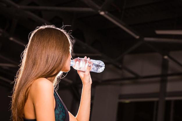 Mulher jovem em forma de água potável no ginásio