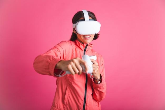 Mulher jovem em forma de esporte usa paletó e óculos de realidade virtual, jogando boxe, luta, rosa