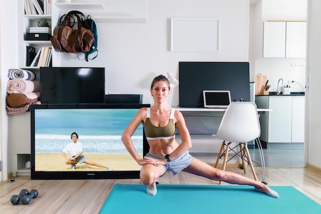 Mulher jovem em forma de ioga fazendo exercícios de alongamento em ambientes fechados perto da tela da tv no isolamento em sua casa