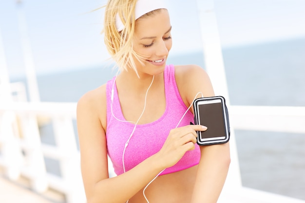 Mulher jovem em forma de sutiã esportivo rosa tocando o telefone no cais sobre o mar