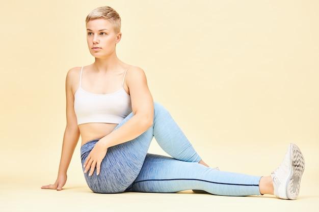Mulher jovem em forma desportiva praticando ioga, fazendo uma variação da postura ardha matsyendrasana ou meio senhor que energiza a coluna e estimula a digestão, sentada no chão com um joelho dobrado, torcendo