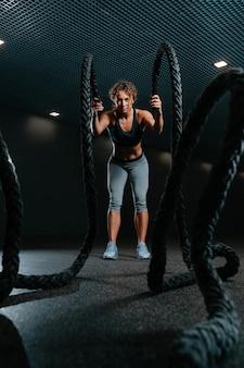 Mulher jovem em forma está envolvida em um ginásio de treinamento funcional, realizando exercícios de crossfit com ro de combate.