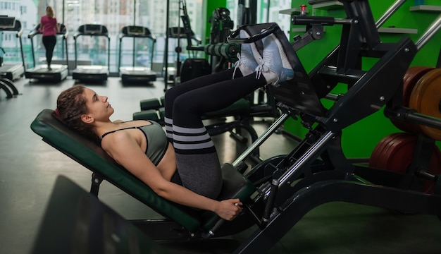 Mulher jovem em forma fazendo leg press em uma máquina de exercícios na academia