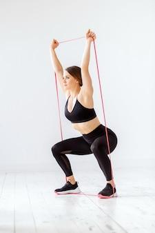 Mulher jovem em forma fazendo um agachamento poderoso