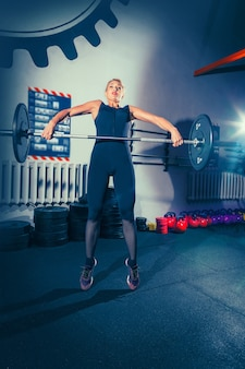 Mulher jovem em forma levantando halteres e malhando em uma academia