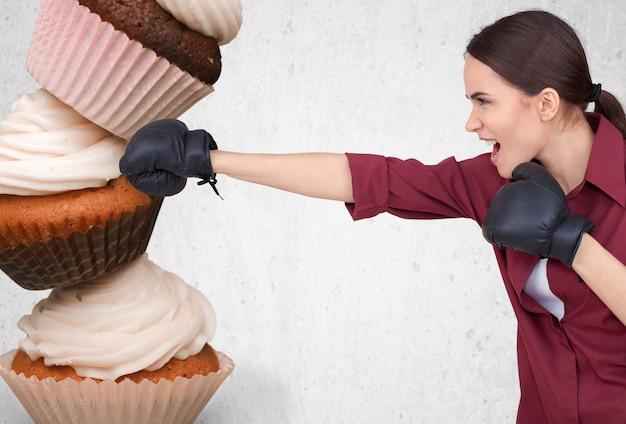 Mulher jovem em forma lutando contra fast food