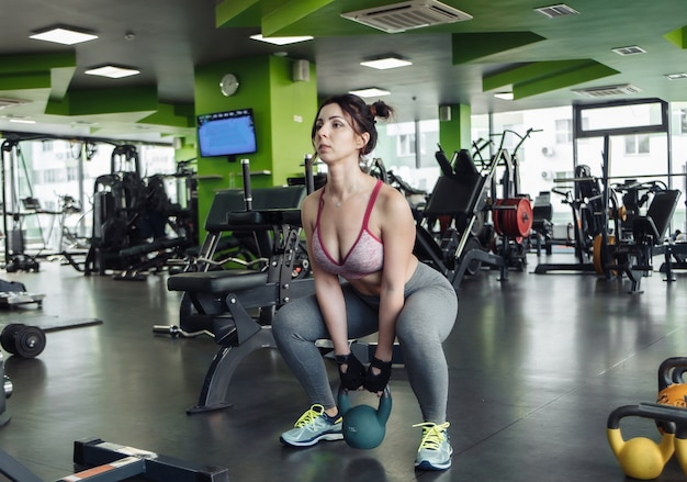 Mulher jovem em forma praticando agachamento com um kettlebell na academia