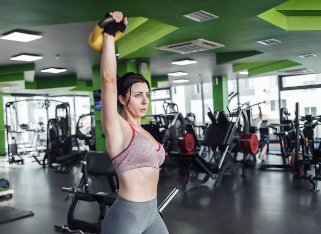 Mulher jovem em forma praticando supino com uma mão com kettlebell na academia
